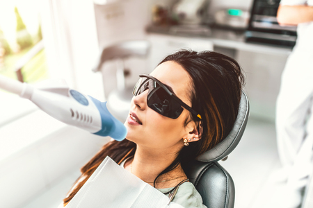Teeth whitening in dental clinic for female patient Stock Photo - 97545791