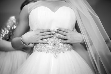 Beautiful bride dressing up before wedding ceremony