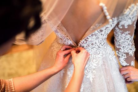 Pretty bride dressing up before wedding  Stock Photo
