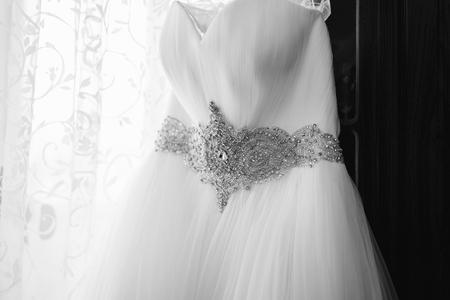 Beautiful wedding dress hang in the bride's room