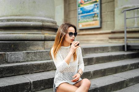 Pretty woman smoke electronic cigarette outdoor