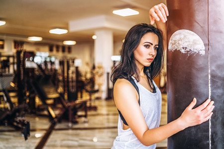 Pretty sporty girl near punching bag in the gym