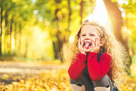 Pretty little girl have fun in the park, autumn time