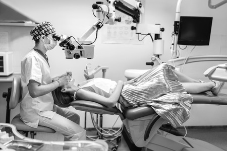 Dentist examine oral cavity of female patient with microscope