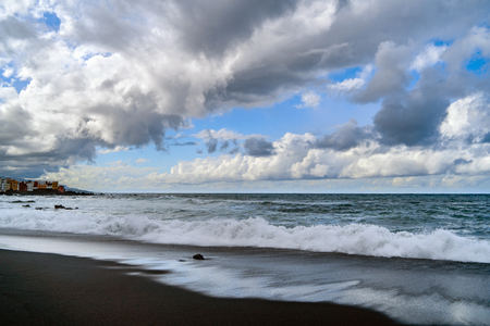 Landscape of mountains and ocean with cloudy sky and black beach Stock Photo
