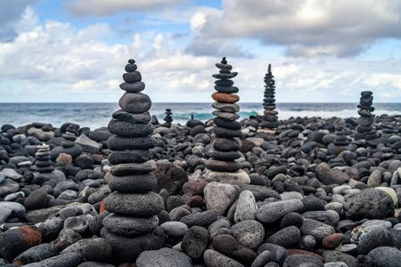 Many stone stacks on the beach near ocean