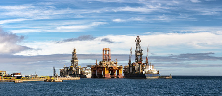 Panorama of the oil drilling platform in the ocean with transportation ships and beautiful sky