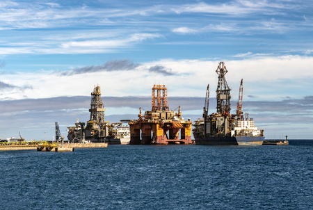 Oil drilling platform in the ocean with transportation ships and beautiful sky