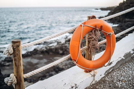 Red emergency lifebuoy hanging on fence near beach