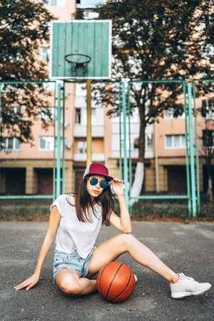 Pretty young sporty girl with basketball ball outdoor