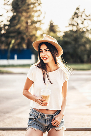 Pretty brunette tourist girl with cup of cold coffee outdoor