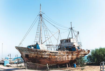 Old rusty fishing ship standing on land near sea