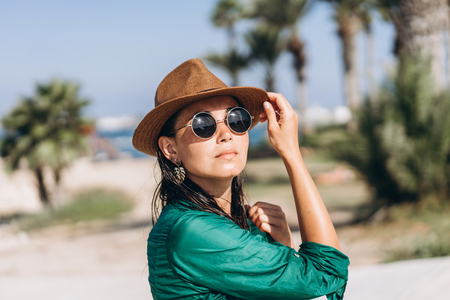 Cute pan asian girl in hat and sunglasses in green pareo walking on the seaside