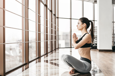 Young slim attractive woman with long hair practicing yoga indoors Reklamní fotografie - 118613273