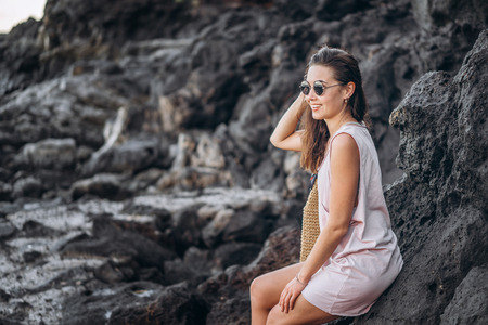 Pretty long hair brunette tourist girl relaxing on the stones near sea Foto de archivo