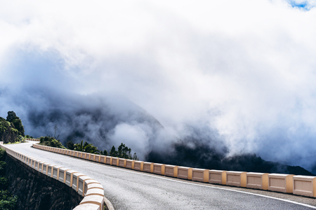 Empty road high in the mountains with cloudy foggy sky Stock Photo