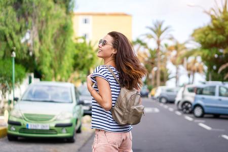 Pretty long hair tourist girl walking on the street