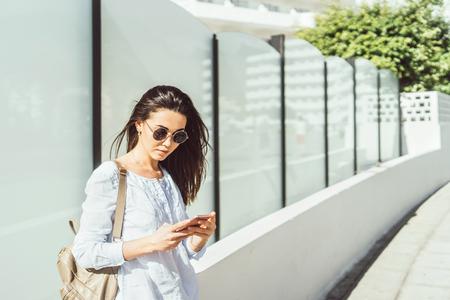 Pretty brunette girl outdoor  using smart phone