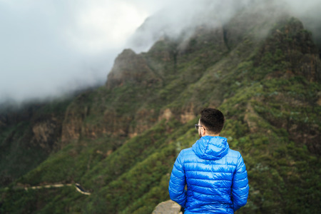 Man in blue jacket relaxing in the mountains with cloudy sky