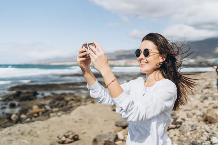Pretty happy brunette girl with smart phone on the beach near ocean
