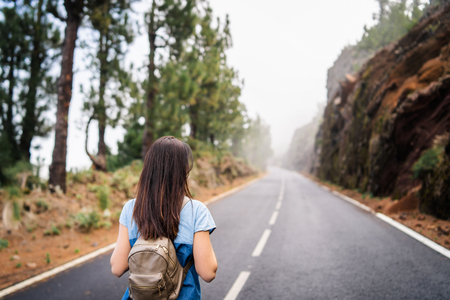 Rear view of long hair brunette girl walking on the foggy road in the mountains