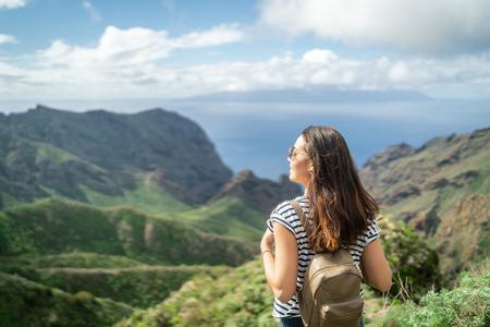 Pretty tourist brunette girl relaxing near mountains