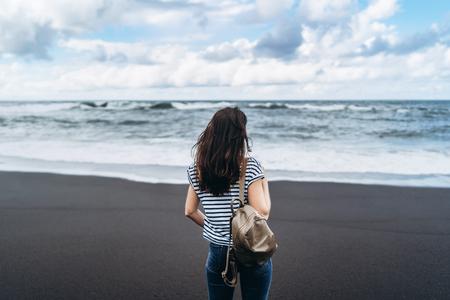 Pretty brunette girl walking on the black sand beach