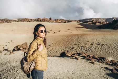 Pretty tourist brunette girl walking near mountains