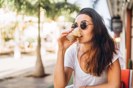 Pretty long hair brunette girl enjoy coffee in street cafe