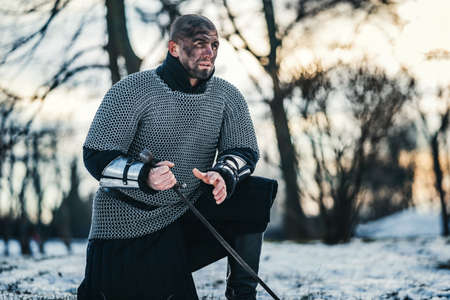 A medieval warrior in chain mail armor kneeling with his sword in his hand and dirty face after the battle. Background of fortress and snow. Banque d'images - 150875044