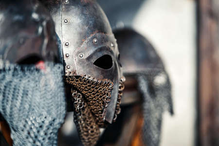 Profile of medieval old knightly helmets for protection in battle. Heavy headgear on a stand. Medieval armor concept. Stock Photo