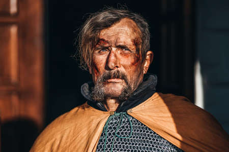 Portrait of a medieval senior warrior man in armor after a battle with dirty and blood-smeared face. Banque d'images