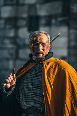 Portrait of a medieval senior warrior man in armor after a battle with dirty and blood-smeared face.