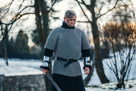 A medieval warrior in chain mail armor kneeling with his sword in his hand and dirty face after the battle. Background of fortress and snow.
