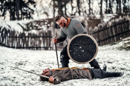 The process of a medieval battle in the snow. A soldier in armor kills an enemy with a sword.