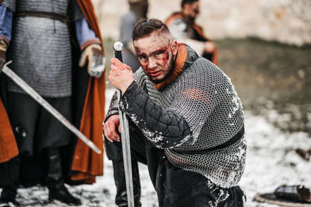 The evil emotions of a young warrior who goes to battle with the sword. Battle near the castle in winter on the background.