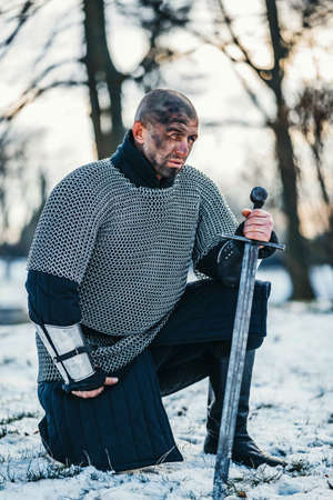 A medieval warrior in chain mail armor kneeling with his sword in his hand and dirty face after the battle. Background of fortress and snow. Banque d'images - 150875202
