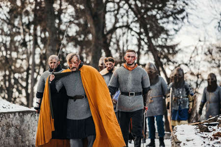 Photo of knights in armor with swords during the war. Evil emotions of a warrior who goes to battle with the sword.