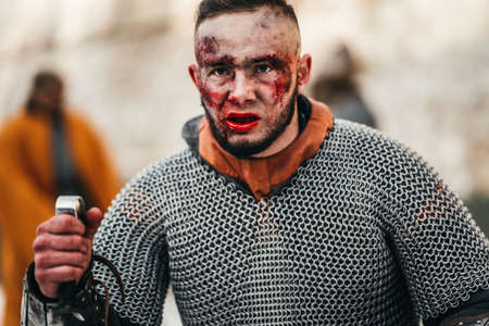 The evil emotions of a young warrior who goes to battle with the sword. Battle near the castle in winter on the background. Imagens