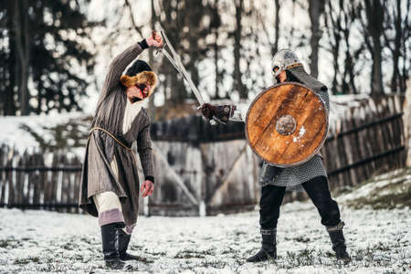 Two ancient warriors in armor with weapons fighting with swords in the snow.