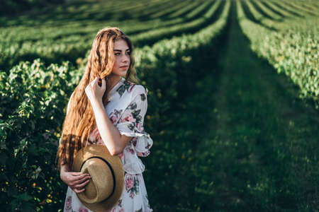 Portrait of a beautiful young woman with curly hair and freckles face. Woman in dress and hat posing in wheat field at sunset and looking at camera.