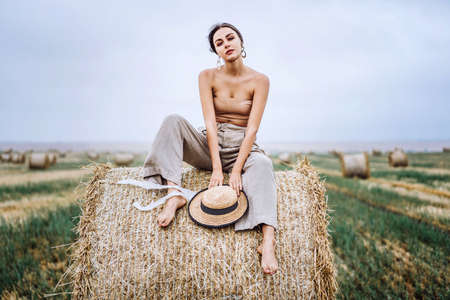 Brunette in linen pants and bare shoulders sitting on a hay bales in warm autumn day. Woman looking at camera. Behind her is a wheat field.