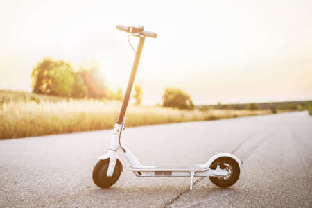 White electric scooter, stand in the middle of the road in the countryside. Content technologies. Sunset time. New movement. 스톡 콘텐츠