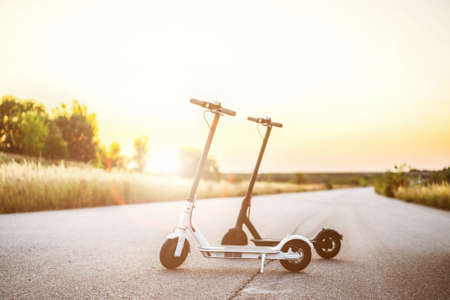 Two electric scooters, black and white, stand in the middle of the road in the countryside. Content technologies. Sunset time. New movement. 스톡 콘텐츠