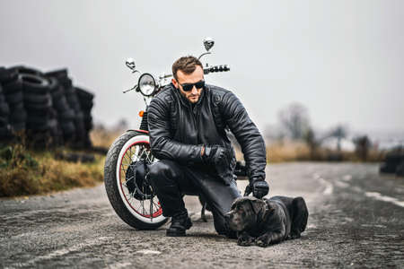 Bearded man in sunglasses and leather jacket looking at the camera while sitting on a motorcycle on the road. Behind him is a row of tires.