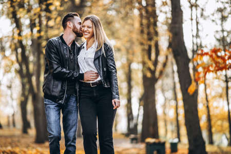 Sunny portrait of a young loving couple walking in the autumn park. They hug and smile, enjoy a walk.