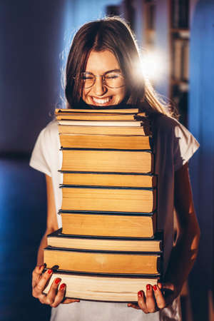 Young girl student with glasses in library smiling and carries stack of books. Exam preparation. 免版税图像