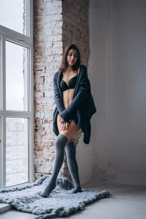 Young brunette in black underwear, knitted knee pads and cardigan standing near window and brick wall in a warm blanket.