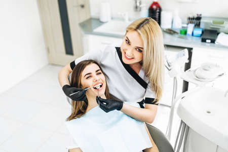 Pretty young female dentist making examination and treatment for young female patient in dental clinic Stock fotó