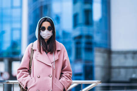Female in medical mask outdoors in the empty city. Health protection and prevention of virus outbreak, coronavirus, COVID-19, epidemic, pandemic, infectious diseases, quarantine concept Banque d'images